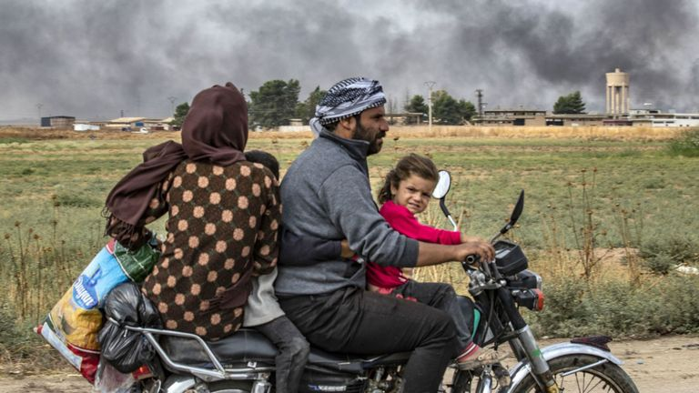 "Members of a Syrian family use a motorcycle to flee the countryside of the northeastern Syrian town of Ras al-Ain on the Turkish border, toward the west to the town of Tal Tamr on October 19, 2019. The smoke behind them is from burning tyres used to impede visibility from warplanes. - Turkey's President Recep Tayyip Erdogan fired off a fresh warning today to ""crush"" Kurdish forces as both sides traded accusations of violating a US-brokered truce deal in northeastern Syria. (Photo by Delil SOULEI"