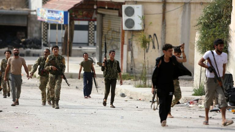 "Turkey-backed Syrian fighters walk in a street near a position that they are holding in the Syrian border town of Ras al-Ain on October 19, 2019. - Turkey's President Recep Tayyip Erdogan fired off a fresh warning today to ""crush"" Kurdish forces as both sides traded accusations of violating a US-brokered truce deal in northeastern Syria. (Photo by Nazeer Al-khatib / AFP) (Photo by NAZEER AL-KHATIB/AFP via Getty Images)"